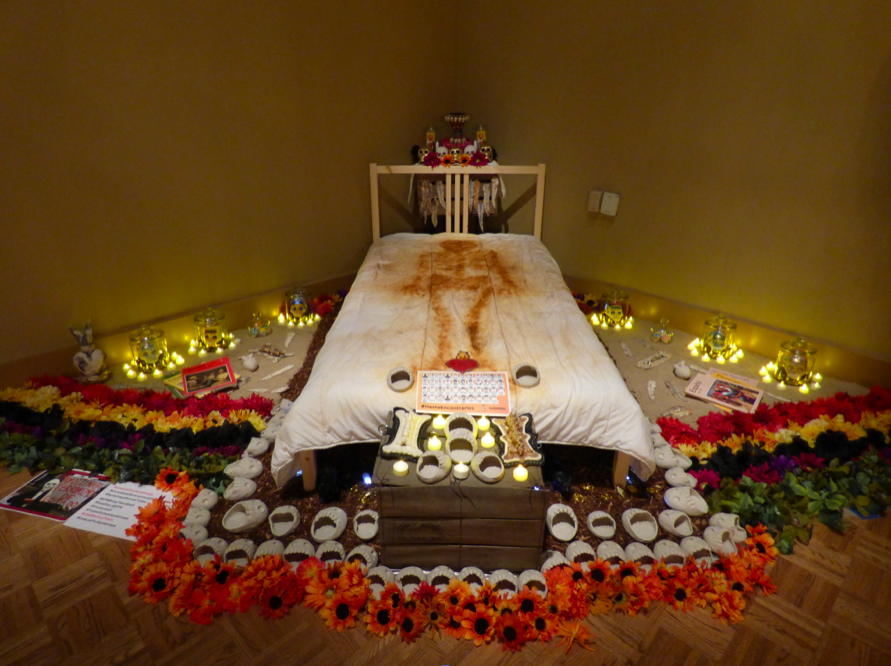 Ayotzinapa, 2014,  Bed, sand, salt, unfired clay, silk flowers, elementary school books from Mexico, sugar skulls and bullet shells Image by Larry McMann, courtesy of the artist