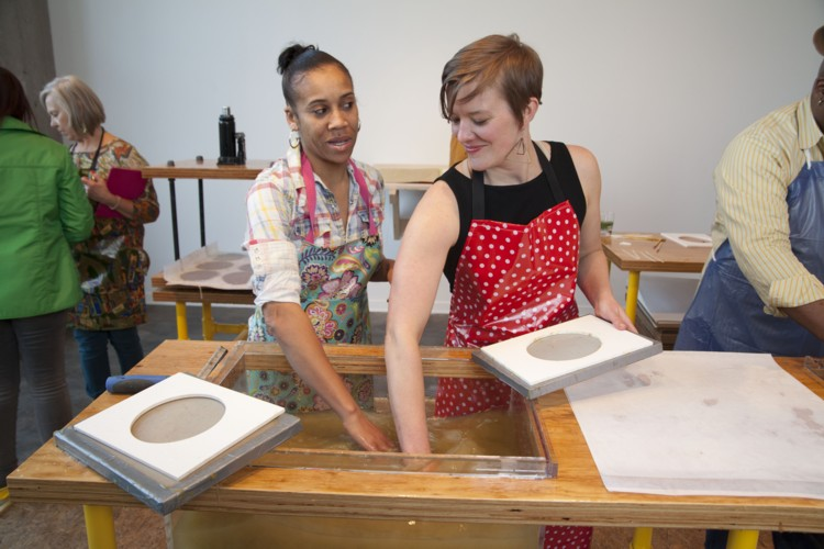 The More We Get Together, artist with gallery visitor at the hand-papermaking station, 2015. Courtesy of the artist.