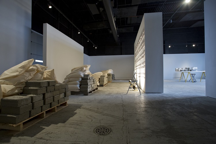 Full Time, 2015, concrete, muslin cloth, embroidery thread, plastic trash bags, wooden molds, sewing machine, cement mixer, shovels, palettes, clock, coffee pot, newsprint, other found and fabricated items, La Esquina Gallery, Kansas City, MO. Photography by Aaron Paden.